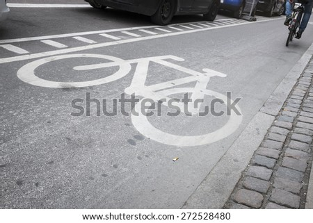 bike lane in the city, with biker going by in the background - stock photo