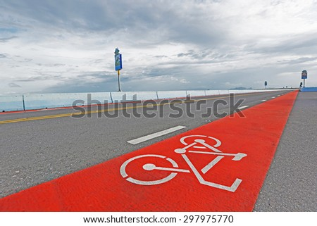 Bike lane on elevated road that runs through the field. - stock photo