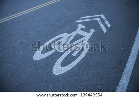 Bike lane route sign in blue and white painted on asphalt - stock photo
