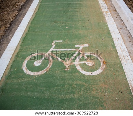 Bike lane signs painted onto a green bike lane ( Bike lane, road for bicycles )