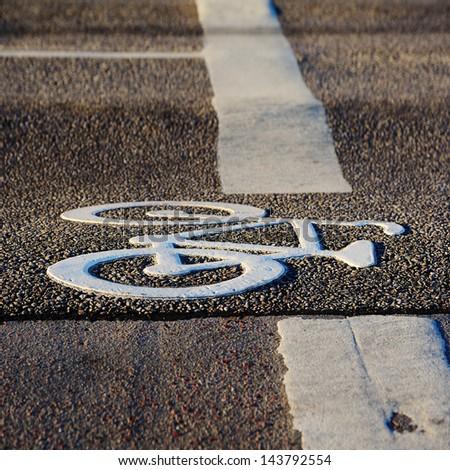 Bike lane symbol in sunset - stock photo