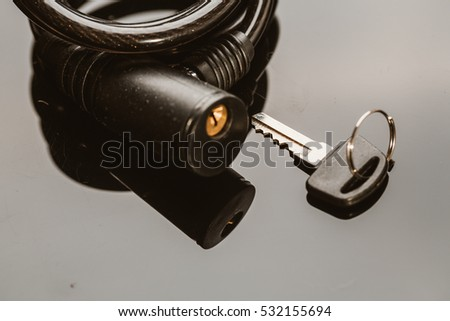 Bike lock with key on a dark background.