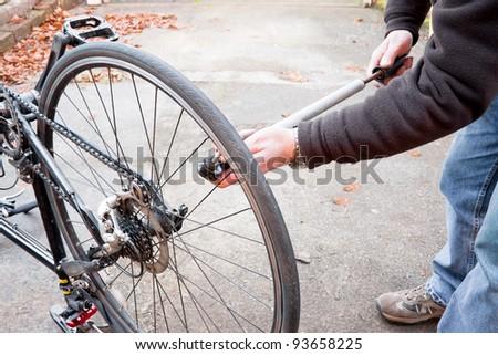 bike maintenance pumping up tyre - stock photo