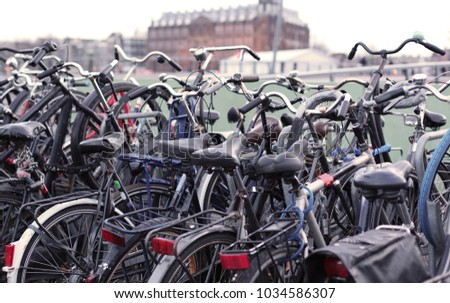 Bike parking in the city center of Amsterdam, the Netherlands. Beautiful building and water canal on the background, vintage effect