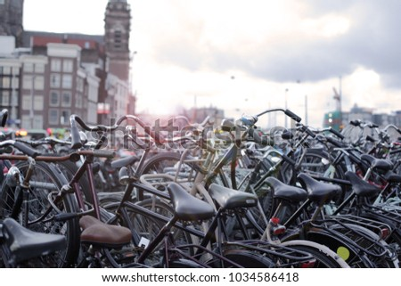 Bike parking in the city center of Amsterdam, the Netherlands. Beautiful building on the background. Toned image with lightening effect