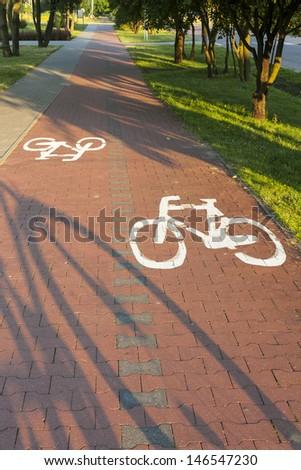 Bike path with a symbol of bike, shadow of bike on a cycling path.  - stock photo