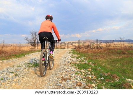 Bike rider on country side road under cloudy sky