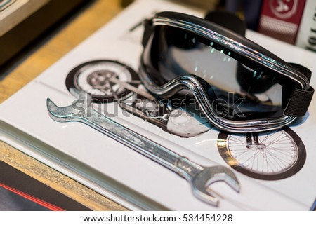 Bike riding glasses put on the books and wrench.