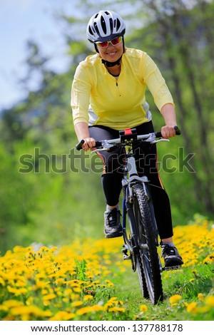 Bike riding - woman on bike, active adult concept - stock photo