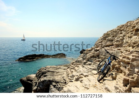Bike, rocks and boat Description: Bicycle and sailboat on the coastline - stock photo