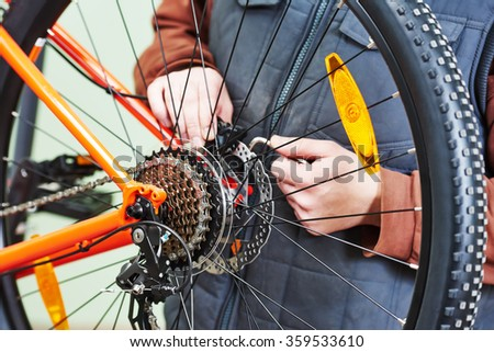 Bike service: mechanic serviceman repairman installing assembling or adjusting bicycle gear on wheel in workshop - stock photo
