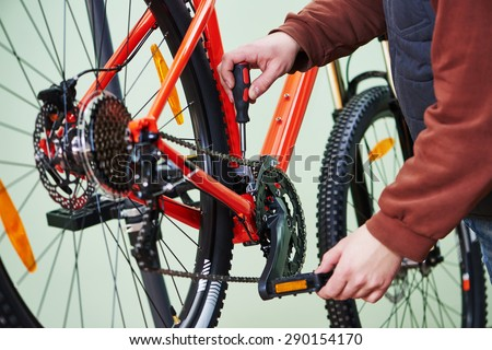 Bike service: mechanic serviceman repairman tuning and assembling or adjusting bicycle chain in workshop - stock photo