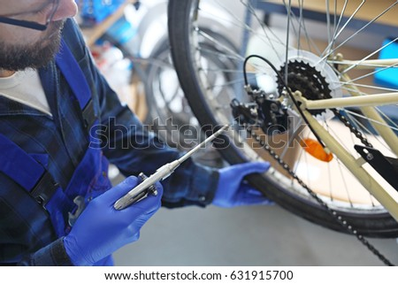 Bike service. The mechanic in the bike service cleans the bicycle with compressed air.