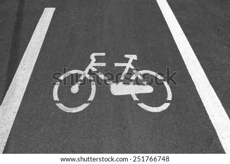 Bike Sign on Asphalt. White markings representing a bicycle in a route reserved for bikes - stock photo