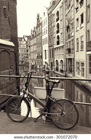 Bike stands on bridge over a canal in Amsterdam - the capital of the Netherlands. - stock photo
