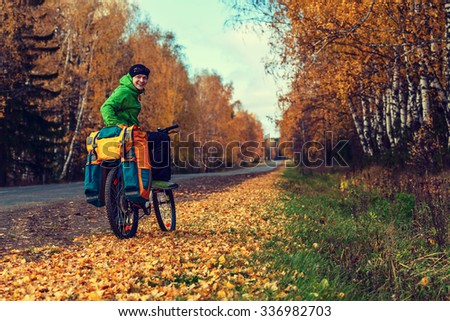 Bike traveler with a backpack on the autumn road