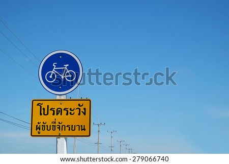 Bike warning sign on blue sky in Thailand. ( Bike warning text in THAI language ) - stock photo