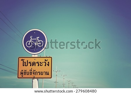 Bike warning sign on blue sky in Thailand with vintage tone ( Bike warning text in THAI language ) - stock photo