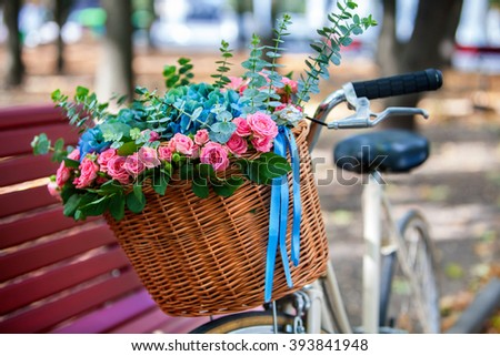 Bike with basket of flowers in spring park near bench. - stock photo