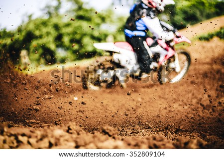 Biker accelerating during a motocross race with flying mud and debris - stock photo