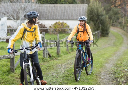 Biker couple interacting while cycling in countryside track