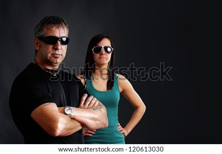 Biker couple: tough guy with tattoos and black sunglasses, arms crossed, looking at camera with pretty young brunette woman, studio shot over black. - stock photo
