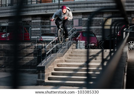 Biker doing double peg grind down the hand rail over the stairs - stock photo