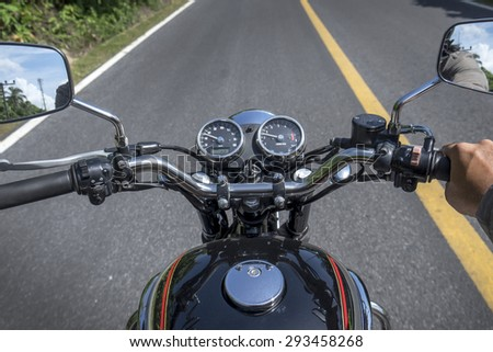 Biker driver riding motorcycle on an asphalt road through forest  - stock photo