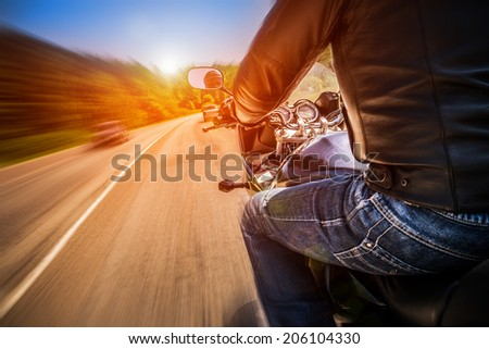 Biker driving a motorcycle rides along the asphalt road. - stock photo