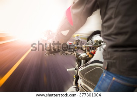 Biker driving a motorcycle rides along the asphalt road - stock photo