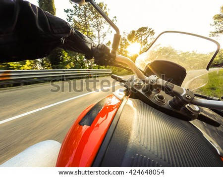 Biker driving a motorcycle rides along the asphalt road. First-person view - stock photo