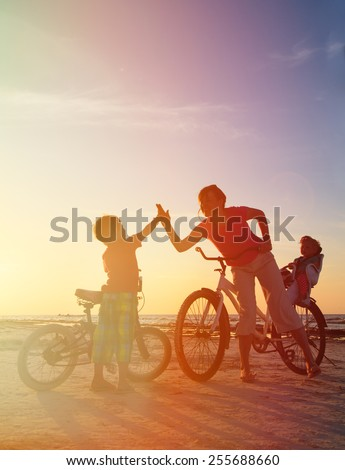 Biker family silhouette at sunset, mother with two kids on bikes