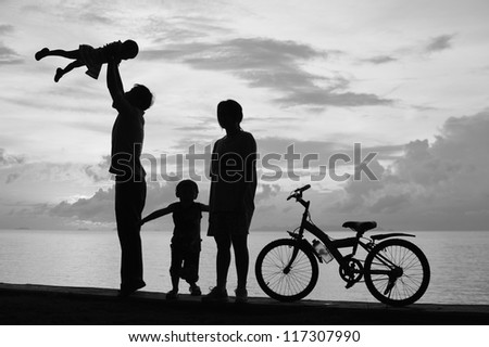 Biker family silhouette  at the beach at sunset.