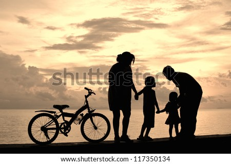 Biker family silhouette  at the beach at sunset. - stock photo
