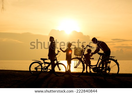 Biker family silhouette , family on the beach at sunset. - stock photo