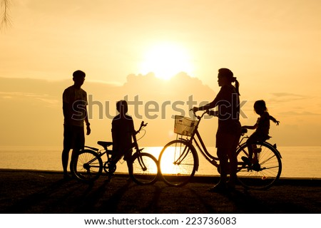 Biker family silhouette , family on the beach at sunset.