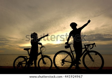Biker family silhouette on the beach at sunset.