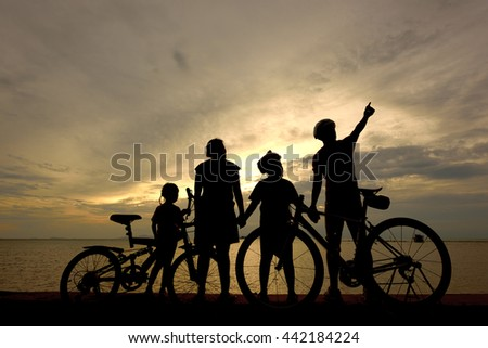 Biker family silhouette on the beach at sunset. - stock photo