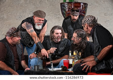 Biker gang members talking and drinking with weapons