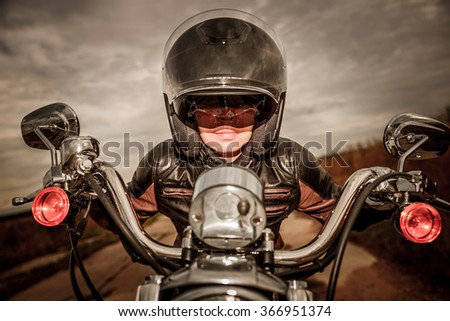 Biker girl in a leather jacket and helmet on a motorcycle. Filter applied in post-production. - stock photo