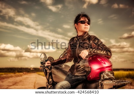 Biker girl in a leather jacket and sunglasses sitting on motorcycle - stock photo