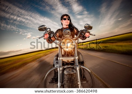 Biker girl in a leather jacket on a motorcycle - stock photo