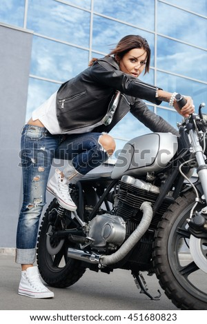 Biker girl in a leather jacket tries to start the vintage custom motorcycle