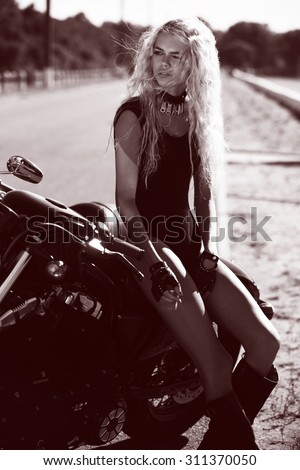 Biker girl in a leather short on a motorcycle