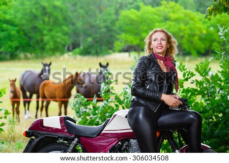 Biker girl in leather jacket on a motorcycle over the background of horses