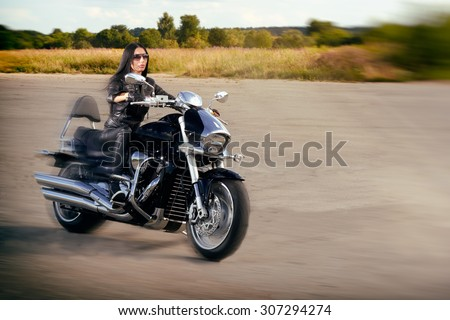 Biker girl in leather jacket riding on a motorcycle. - stock photo