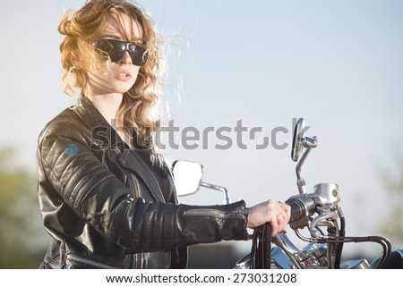 Biker girl in the  leather jacket on a motorcycle looking at the sunset. - stock photo