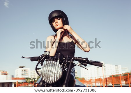 Biker girl sits on vintage custom motorcycle and buttons helmet. Outdoor lifestyle portrait - stock photo