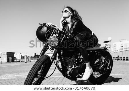 Biker girl sitting on vintage custom motorcycle. Black white Outdoor lifestyle portrait - stock photo