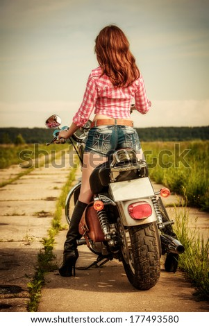 Biker girl with sunglasses and motorcycle - stock photo